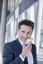 Portrait of smiling businessman using cell phone - RORF00986