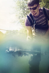 Slovenia, man fly fishing in Soca river catching a fish - BMAF00315