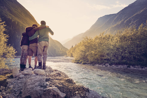 Slovenia, Bovec, three friends at Soca river at sunset - BMAF00330