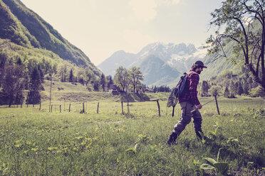 Slovenia, Bovec, angler walking on meadow towards Soca river - BMAF00336