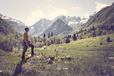 Slovenia, Bovec, man standing on meadow near Soca river - BMAF00339