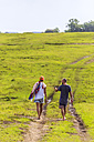 Back view of couple walking barefoot on a meadow - KNTF00871