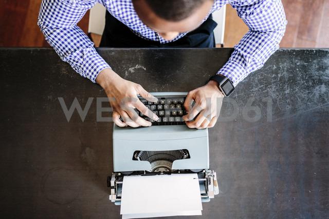 Young man at desk using typewriter - GIOF03136