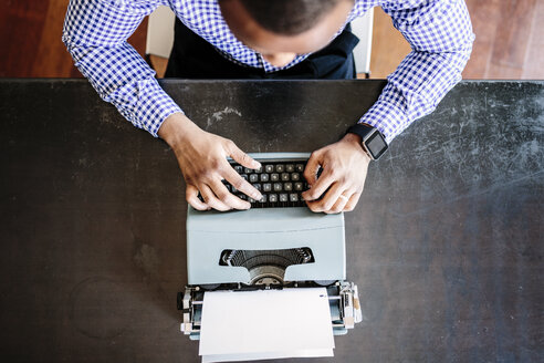 Young man at desk using typewriter - GIOF03136