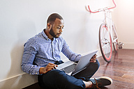 Man using laptop sitting on wooden floor with bicycle in background - GIOF03142