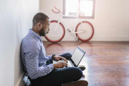 Man using laptop sitting on wooden floor with bicycle in background - GIOF03145