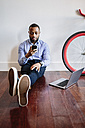 Man sitting on wooden floor with laptop and cell phone and bicycle next to him - GIOF03148