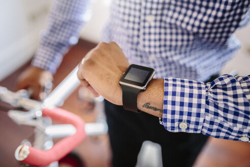Close-up of man checking the smartwatch while holding a bike indoors - GIOF03151