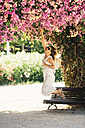 Woman reaching for pink blossoms in park - JPF00268