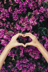 Woman's hands shaping heart in front of pink blossoms - JPF00271