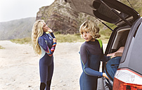 Spain, Aviles, two young surfers at a car on the beach - MGOF03538