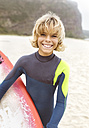 Spain, Aviles, portrait of smiling young surfer on the beach - MGOF03547