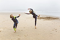 Spain, Aviles, two young surfers warming up before surfing - MGOF03550