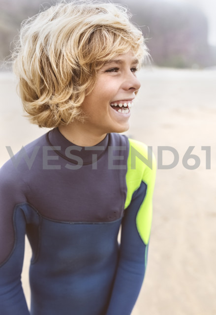 Spain, Aviles, laughing teenage boy in wetsuit on the beach - MGOF03553 - Marco Govel/Westend61