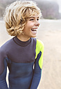 Spain, Aviles, laughing teenage boy in wetsuit on the beach - MGOF03553