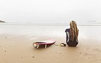 Spain, Aviles, young surfer resting after surfing on the beach - MGOF03559