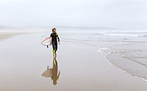Spain, Aviles, young surfer carrying surfboard on the beach - MGOF03562