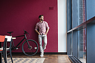 Man with bicycle standing in modern office looking out of window - DIGF02740
