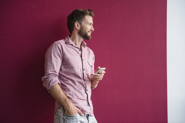 Man standing against purple wall holding cell phone - DIGF02743