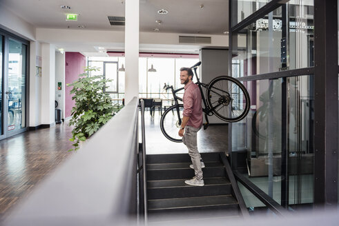 Man with bicycle walking upstairs in modern office - DIGF02746