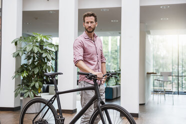 Portrait of man with bicycle in office - DIGF02749