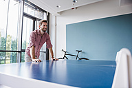 Man in break room of modern office at table tennis table - DIGF02752