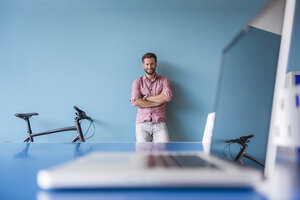 Portrait of smiling man and laptop in break room of modern office - DIGF02758