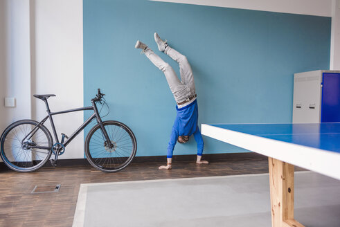 Man doing a handstand in break room of modern office - DIGF02764