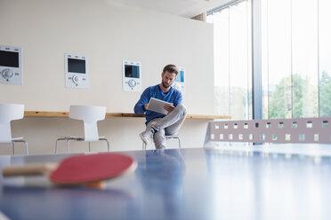 Man using tablet in break room of modern office - DIGF02767
