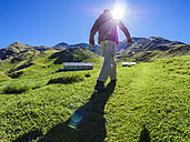 Italy, Lombardy, Sondrio, hiker on alpine meadow on the way to Umbrail Pass - LAF01878