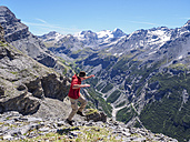 Italy, Lombardy, Sondrio, hiker jumping with view to Stelvio Pass and Ortler - LAF01881