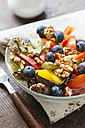 Glass bowl of mixed salad with different raw vegetables, blueberries and walnuts - HAWF00963