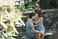 Couple in love hugging on bench in a park - ALBF00156