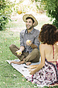 Happy couple having a picnic in a park with man juggling with apples - ALBF00171