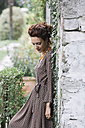 Woman wearing elegant dress leaning against a wall - ALBF00177