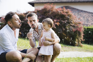 Gay couple playing with their child in the garden - MRAF00228