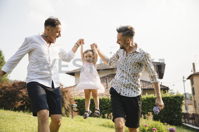 Happy gay couple playing with their child in the garden - MRAF00231