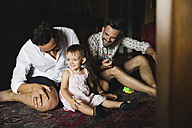 Gay couple playing with their little daughter at home - MRAF00237