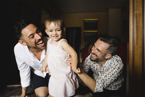 Happy gay couple playing with their little daughter at home - MRAF00240