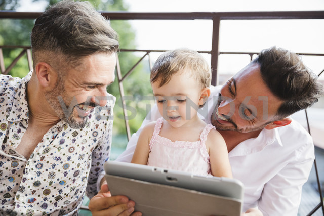Happy gay couple with daughter on balcony using digital tablet - MRAF00246