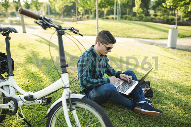 Young man with bicycle using laptop in a park - RAEF01907