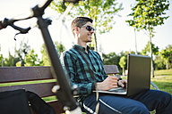 Young man with bicycle using laptop on park bench - RAEF01910