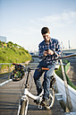 Smiling young man with bicycle looking at smartphone - RAEF01916