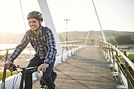 Young man riding bicycle on a bridge at sunset - RAEF01919