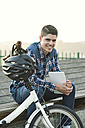 Portrait of smiling young man with folding bicycle and tablet - RAEF01922