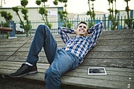 Young man lying and smiling outdoors - RAEF01925