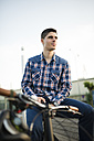 Young man with bicycle outdoors - RAEF01928