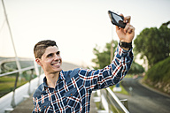 Smiling young man taking a selfie outdoors - RAEF01931