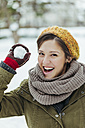 Portrait of laughing woman holding snowball - ZEDF00802