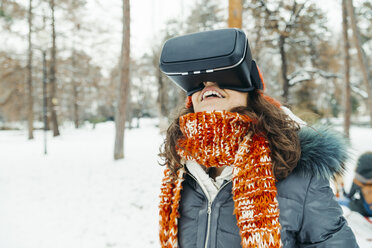 Woman wearing Virtual Reality Glasses in winter landscape - ZEDF00811
